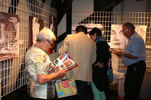 Ausstellung Der Reiz der Frau, Belvedereschlössl Stockerau, Gäste beim Betrachten des Bildbandes und Folders