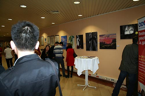 Besucher beim Betrachten der ausgestellten Gemälde